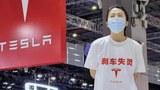 """2021年4月19日,上海车展,特斯拉维权女站在展车上,白色T恤上印有""""刹车失灵""""。"""