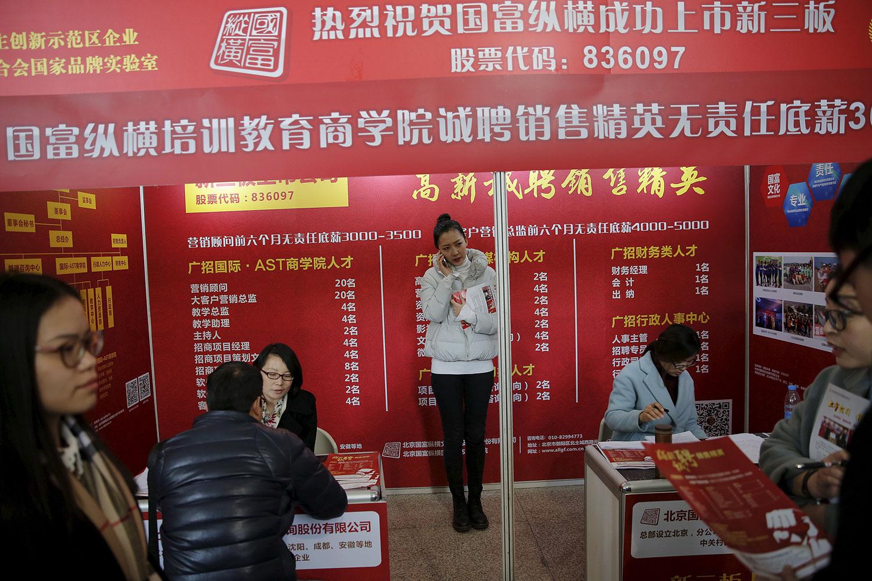 北京的招聘会上与求职者交谈。(路透社)