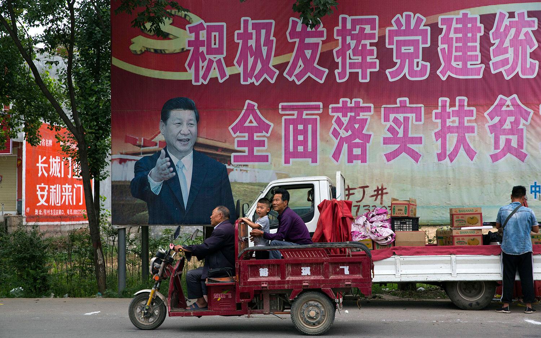 """河南省平顶山市居民经过习近平的海报和""""积极发挥党的建设引领作用,全面实施脱贫攻坚计划""""的部分标语。(美联社)"""