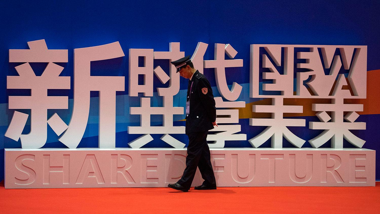 """上海举办的中国国际进口博览会上,一名保安走近""""新时代,共享未来""""的标语。(美联社)"""