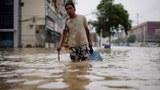 洪灾席卷河南各地,街道有如汪洋,民众提着瓶装水涉水而行。