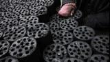 图片:煤炭批发市场上,一名工人正在整理煤砖。